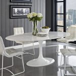 modern white sleek small oval dining table with white metal frame leather chairs beautiful decorative flower and fruit gray tone dining room wall pictures