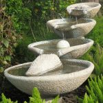 natural stone front yard fountain idea with ladder style and greenery aside lush vegetation