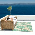 ocean blue flowery motive recycled plastic outdoor rugs open ocean deck wicker sofa white cushions white floor beautiful tree ornament