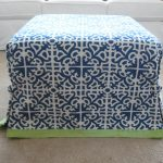 ottoman slip covers in white and blue navy pattern and green accent on its edge decorated in front of the white couch and beige rug