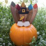 playful outdoor thanksgiving decoration idea with pumpkin design with artificial leave with pop character in the middle of savanna