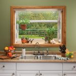 pretty garden windows for kitchens adorned with herb and colorful flower plants located above steel kitchen sink and brown granite countertop and white wooden kitchen cabinets