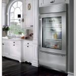 quite large stainless steel glass door refrigerator design in white kitchen with wooden cabinetry and arched window with glass accent