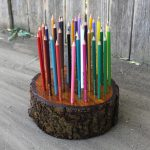 rustic long round colored pencil holder idea made of wood on grey board with rustic wooden deck fence