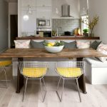 scandinavian corner breakfast nook furniture idea with white banquette and yellow stools and rustic table aside small kitchen with white washed wooden floor