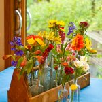 simple beautiful colorful flower arrangement in wooden long vase and bottles
