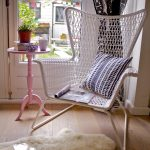 simple but comfortable cozy reading chair idea on wooden floor with faux fur rug and pink round table and glass window