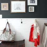 simple design of picture frame target design on black board wall in mud room with bag and jacket and rattan bench