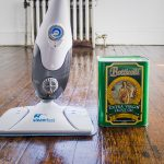 simple designed steam cleaning for wooden floor with adjustment setting and cleaning liquid in green package and dark wooden floor