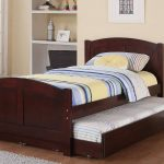 simple modern trundle beds for children with dark wooden bed frame and double bed plus striped bedding set and wooden shelving and beige wall pain color