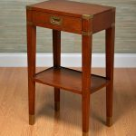 simple wooden campaign side table in brown finishing with drawer beneath plus metal handle and rack underneath decorated with laminate floor