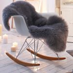 smooth and tender faux sheepskin throw in gray tone on white rocking chair on wooden floor with candelabrum