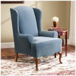 soft blue wingback slipcover sofa design with woodne carved legs and wooden side table with drawer and patterned area rug on wooden floor