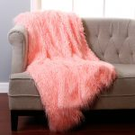 soft peach faux sheepskin throw for gray modern sofa with tuft pattern on wooden floor beneath glass window