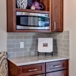 space saver microwave in kitchen counter wooden cabinets with marble countertop and grey subway tile backsplash