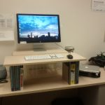 standing desk books telephone wood table laptop
