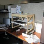 standing desk wood table paper books laptop