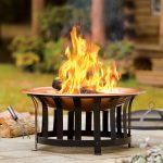 stunning modern chiminea fire pit design with black metal base and copper plate on patio with grassy meadow