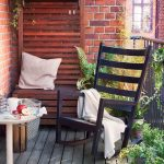 stunning small living space with ikea lawn furniture of black wooden rocking chair and round white table on rustic wooden floor beneath red brick wall and wooden bench