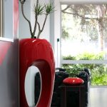 stylish red modern indoor pot design with unique plant on white floor with black seating and open plan
