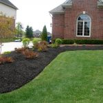 super duper awesome best mulch for landscaping in black color for slope garden with grassy meadow and pine tree and shrub and red brick house design