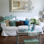 superb white slipcovered sofa with various colors of cushion and vintage coffee table plus luxurious framed mirror and chandeliers and wooden floor