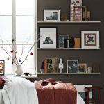 three white metal picture ledge shelf or shelves on bedroom for decorating pictures and collection presented with wooden stool