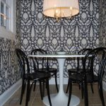 tiny dining space with ikea tulip table decorated with black chairs and stunning pendant lamp and cool wallpaper motif plus tile flooring