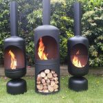 triple black chiminea fire pit idea in tube style with no legs with chimney on grassy meadow with greenery