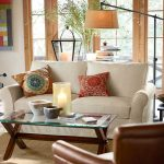 tropical sense interior with white pottery barn sofa slipcover design with patterned cushion and glass coffee table and glass window and creamy area rug