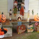 unique and playful outdoor thanksgiving decoration idea on grassy meadow wih painted pumpkin with character picture and fall color flower before a house