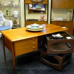 unique designed mid century secretary desk design in yellow tone with drawers and modular elements before cupboard on black marble flooring