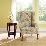 unique patterned white wingback chair slipcover idea with artistic wooden legs aside round wooden side table and large glass window and yellow walland cream area rug