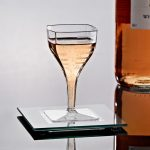 unqiue square wine glass design on square glass tray aside exclusive wine bottle on black top