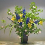 unusual flower arrangements with yellow white green blue flowers in tall blue vase