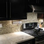 Vintage Design Kitchen With Black Cabinet And Mosaic Stone Backsplash And Cook Top And  River White Granite Countertop