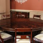 vintage marroon 84 round dining table design with wooden chairs with white bolster in peach room with chandelier