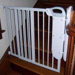 vintage wooden staircase design with wooden railing and white wall and white metal baby gate for top stairs