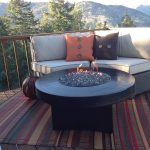 warm stripes Mad Mats recycled plastic outdoor rugs wicker sofa orange brown cushions brown wooden round table open view deck
