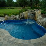 waterfall swimming pool water rocks flower plants