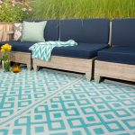 white blue motives recycled plastic outdoor rugs bold blue outdoor wooden sofas flowers pots green grass pastel blue cushions