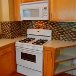 white space saver microwave for small space kitchen with wooden kitchen cabinets and countertop plus tile backsplash