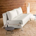 white twin size sleeper sofa for elegant living room made of leather plus metal leg and cushion decorated with small round end table and beige rug