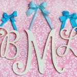 wonderful large decorative letter design in BML shape on pink wall with floral pattern with blue ribbon