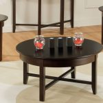 wooden cocktail table sets with dark finishing plus round shape decorated with soft modern rug and light wooden laminate floor