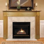 A fireplace with wood mantel and square mirror over the mantel a pair of candle holders a small vase with flowers