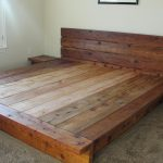 A king platform bed frame with headboard made from hard wood a pair of wooden bedside table