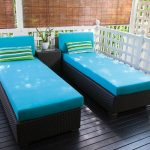 A pair of modern daybed furniture sets for outdoor with blue ocean mattress and multiple colored strips patterned pillowcases a square side table with transparent glass top