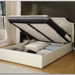 A white king platform bed frame with under storage and white headboard