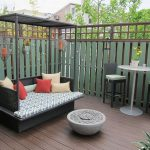 An outdoor daybed furniture with shade and thiner mattresss and red and cream pillows a pair of bar stools and white round table for outdoor spot